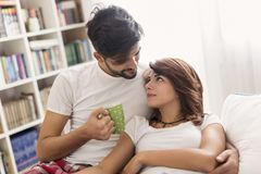 Loving couple cuddling after waking up. Loving couple cuddling and drinking coffee after waking up in bed stock images