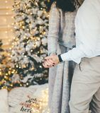 Couple of lovers dancing near the Christmas tree close up stock images