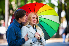 Loving couple on date under umbrella in good autumn day. Stock Image