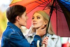 Loving couple on a date under umbrella Stock Photos