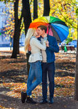 Loving couple on date under umbrella kissing in fall park. Royalty Free Stock Image