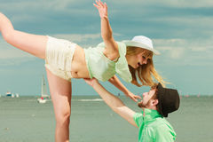 Loving couple dating on sea coast. Summer holidays love relationship and dating concept - romantic playful couple flirting on sea shore Royalty Free Stock Image