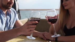 Loving couple decides to drink some wine on terrace by the sea. stock video footage