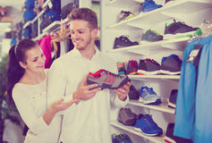 Loving couple deciding on new sneakers in sports store Royalty Free Stock Images
