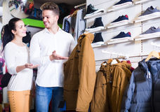 Loving couple deciding on warm suit in sports store Royalty Free Stock Photos