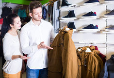 Loving couple deciding on warm suit in sports store Stock Photography