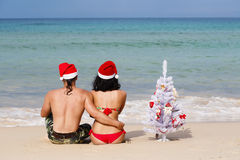 Loving couple in a dress of a sat of Claus on a beach Royalty Free Stock Photo