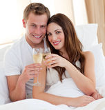 Loving couple drinking champagne lying in bed Stock Images