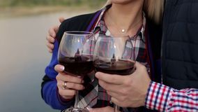 Loving couple drinks red wine on the river bank. Loving couple drinks red wine from large glasses on the river bank. Close-up stock video footage