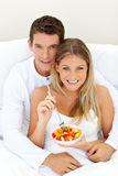 Loving couple eating fruit lying on their bed Royalty Free Stock Photo