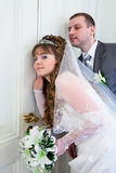 Loving couple eavesdropping behind door Stock Photos