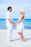Loving couple embracing on the beach. Loving couple walking and embracing on a tropical summer beach Royalty Free Stock Photography