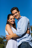Loving couple embracing each other against clear blue sky Royalty Free Stock Image
