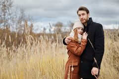 Loving couple embracing in the field, autumn landscape. Man and woman in autumn clothes in nature, love and tenderness in touch Stock Photo