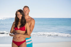 Loving couple embracing one another while looking at camera. Loving couple on the beach embracing one another while looking at camera Royalty Free Stock Photography