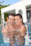 Loving couple embracing in private pool Stock Photos
