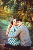 Loving couple embracing sitting in the woods. A pair of lovers sitting in the forest on a tree and hugging at sunset Royalty Free Stock Photography