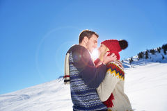 Loving couple embracing in winter park. They put colored caps and scarves. Stock Images