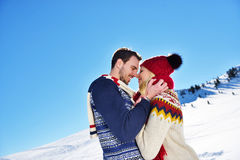 Loving couple embracing in winter park. They put colored caps and scarves. Royalty Free Stock Photo