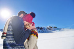 Loving couple embracing in winter park. They put colored caps and scarves. royalty free stock photos