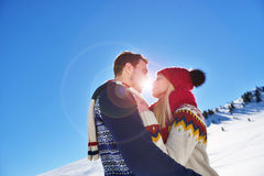 Loving couple embracing in winter park. They put colored caps and scarves. Stock Photo