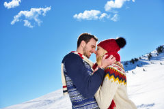 Loving couple embracing in winter park. They put colored caps and scarves. Royalty Free Stock Images