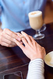 Loving couple engaging in restaurant. Will young marry me. Young man is asking his girlfriend to be his wife. He is wearing ring on female finger. Focus on their Royalty Free Stock Photos
