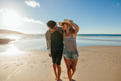 Loving couple enjoying a day on beach. Loving young couple enjoying a day on beach. Beautiful couple walking on the seashore on a summer day Royalty Free Stock Photos