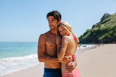 Loving couple enjoying holidays on the beach. Portrait of happy young women with her boyfriend on the  shore. Loving couple on the beach enjoying summer holidays Royalty Free Stock Photos
