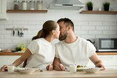 Loving couple enjoying meal kissing sitting at dining kitchen ta. Loving sensual couple enjoying homemade cooked meal kissing sitting at dining table in the Stock Photo
