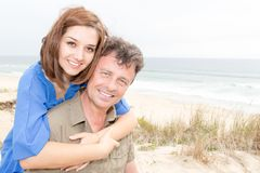 Couple enjoying vacation joyful man giving piggyback ride to his beautiful girlfriend stock photos