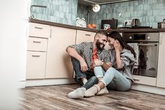 Loving couple feeling memorable while sitting in the kitchen. Feeling memorable. Loving couple feeling memorable while sitting in the kitchen waiting for their stock photography