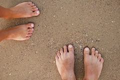 Loving couple feet in the sand Royalty Free Stock Photos