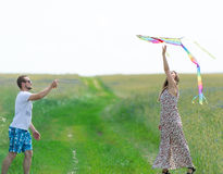 Loving couple are fling kite on a meadow. Loving couple are fling a kite on a spring meadow royalty free stock image