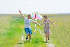 Loving couple are fling kite on a meadow. Loving couple are fling a kite on a spring meadow royalty free stock photo