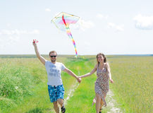 Loving couple are fling kite on a meadow. Loving couple are fling a kite on a spring meadow stock photography