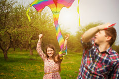 Loving couple are fling a kite on a spring meadow. Couple are fling a kite on a spring meadow royalty free stock images