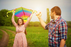 Loving couple are fling a kite on a spring meadow Stock Photography