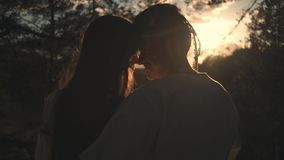 A loving couple in folk costumes hugs at sunset in the forest stock video