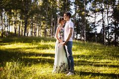 Loving couple in the forest. Beautiful girl with dark hair and brown eyes with a wreath on head in summer dress hugging a men in awhite shirt on a green royalty free stock image