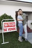 Loving Couple In Front Of House For Sale. Portrait of a happy couple embracing in front of house for sale royalty free stock photo