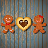 Loving couple of gingerbread cookies and chocolate heart cookie Stock Photos