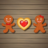 Loving couple of gingerbread cookies and strawberry heart cookie Stock Photos