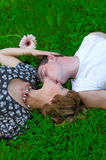 Loving couple on grass. Teenagers: girl and fellow are lying on green grass and kissing. Green grass around them and flower Stock Images