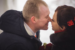 The loving couple, the groom and the bride, kiss on the street in the winter Royalty Free Stock Photo