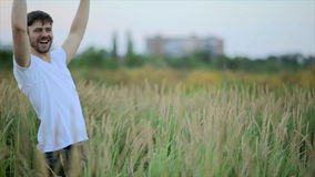 A loving couple.  Guy kisses a woman and then jokingly drops her. Fun young man and woman holding hands and whirling in the field stock footage