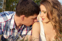 Loving couple of guys and girls lying on the grass on the meadow, man kissing a girl on the shoulder Stock Photo