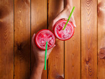 Loving couple hands holding colorful chilled cocktails toasting cheers Stock Image