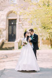 Loving couple, handsome groom embracing his charming bride in park. Old vintage building at background Royalty Free Stock Photos
