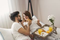 Loving couple having breakfast in bed royalty free stock photography